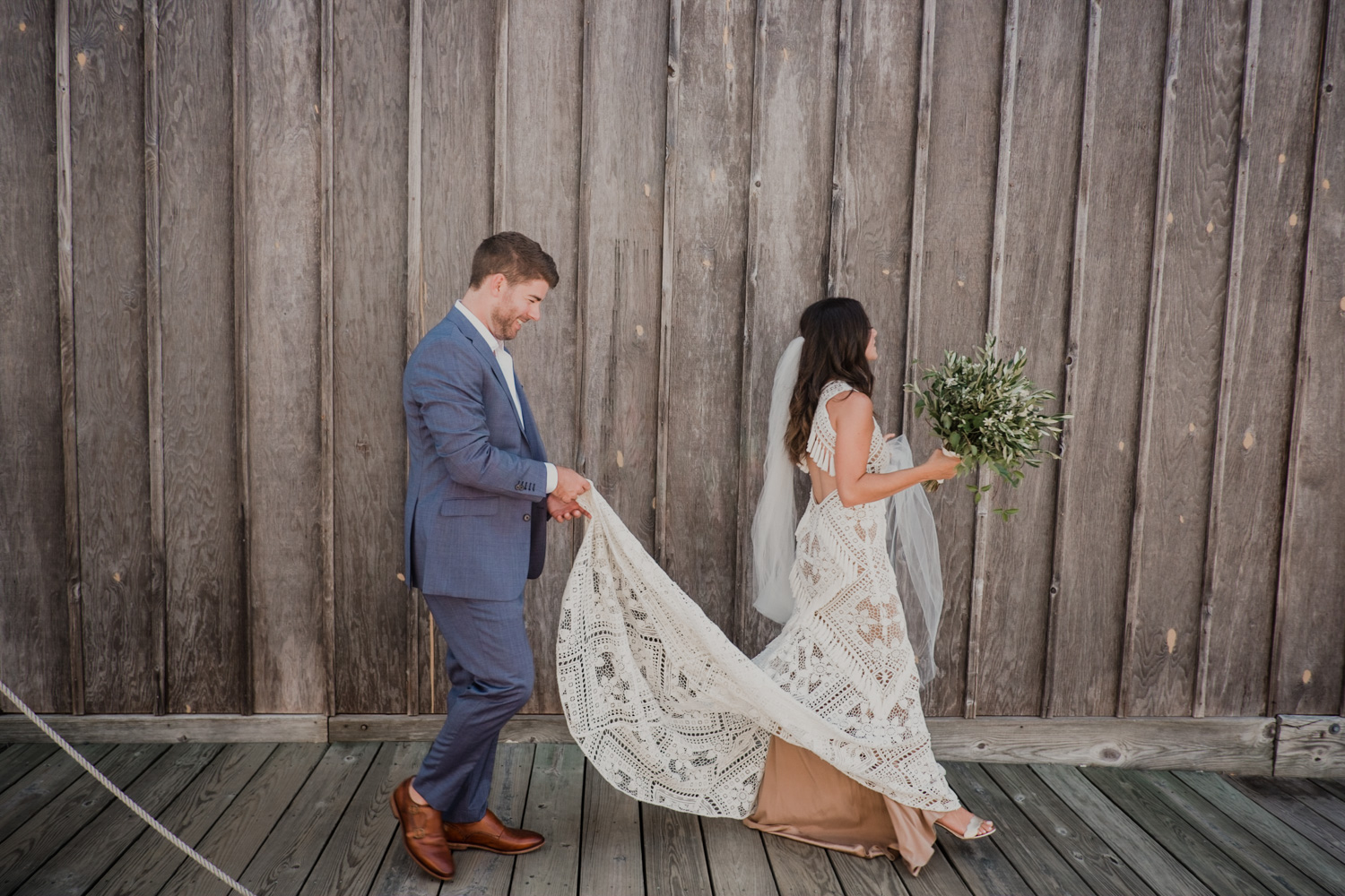 groom holds dress for bride as they walk across the docks after first look