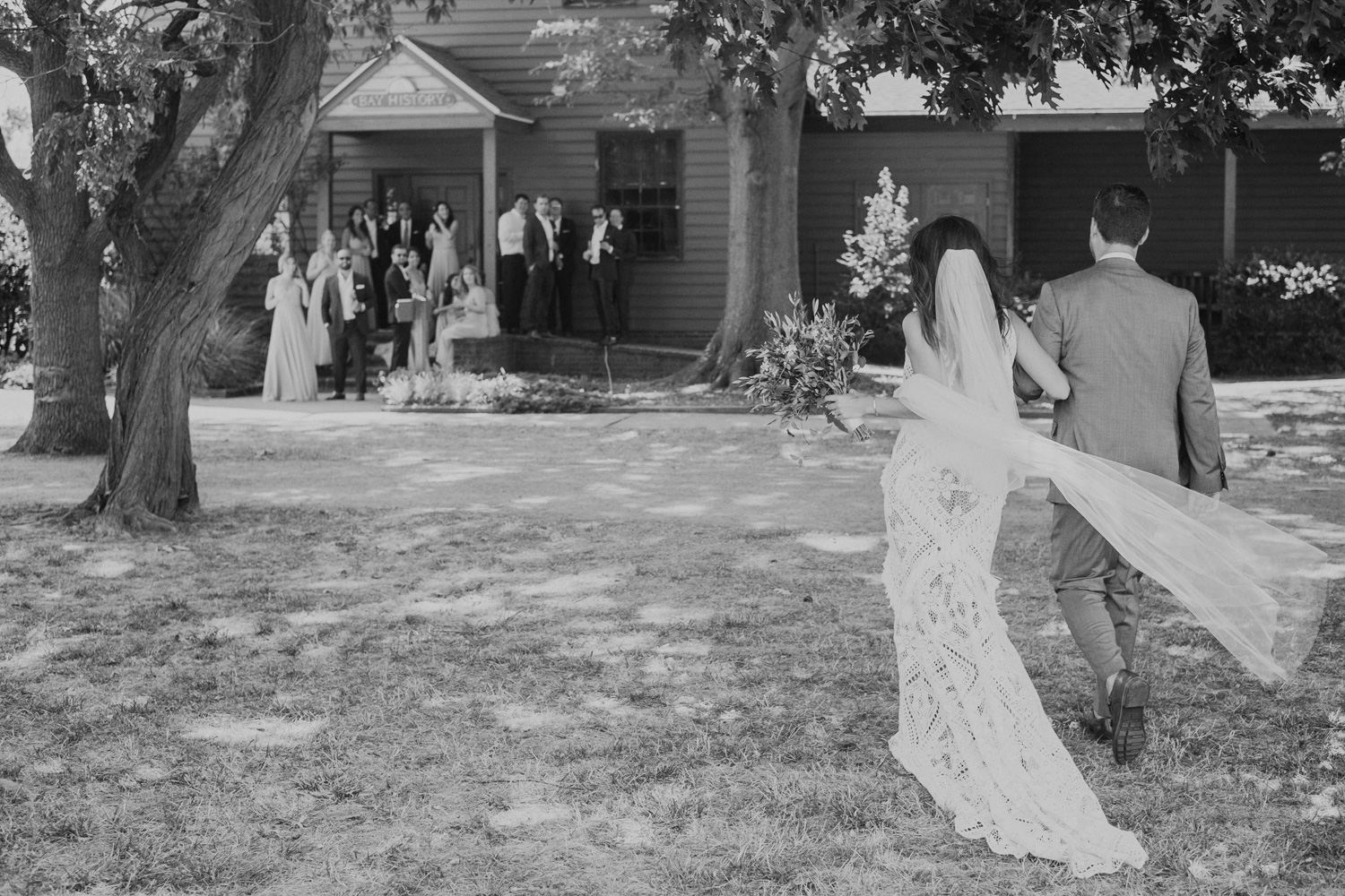 bride and groom walk towards wedding party after first look across a field
