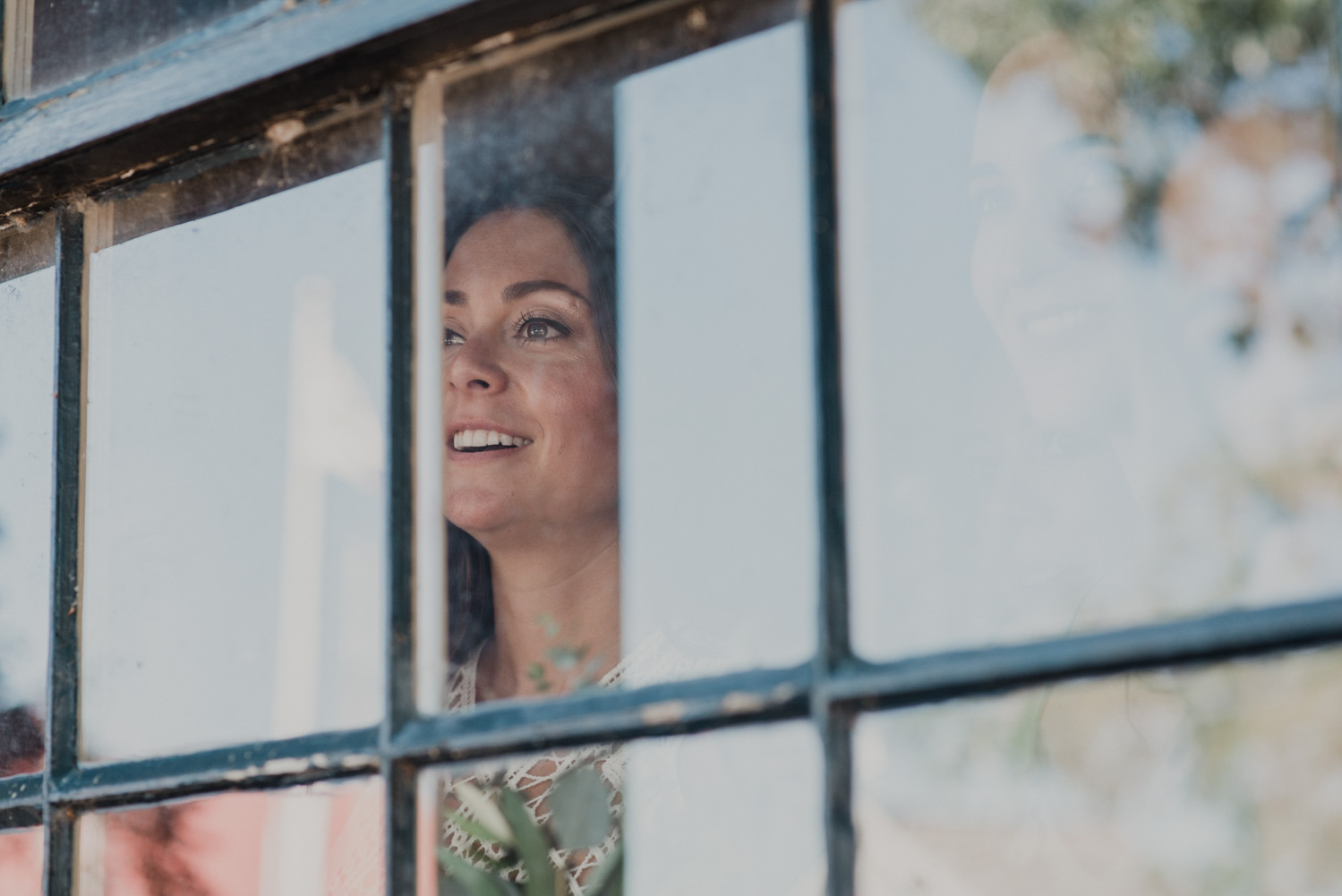 bride looks out window watching guests mingle before wedding