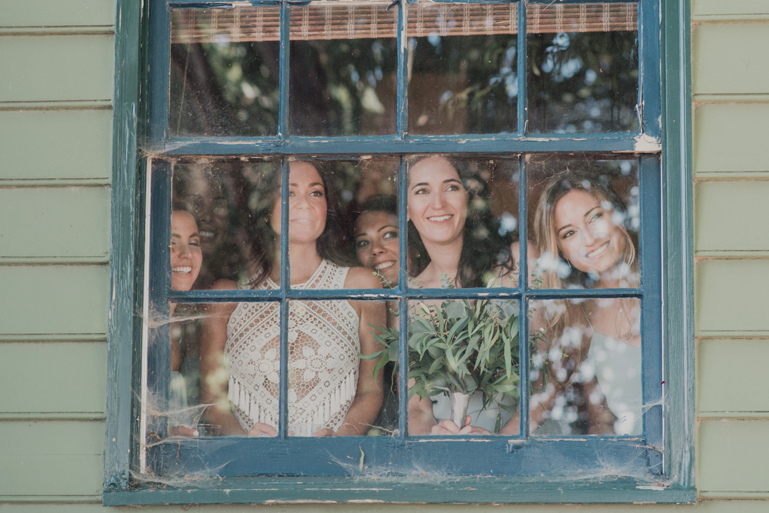 bride and bridesmaids look out window as guests arrive