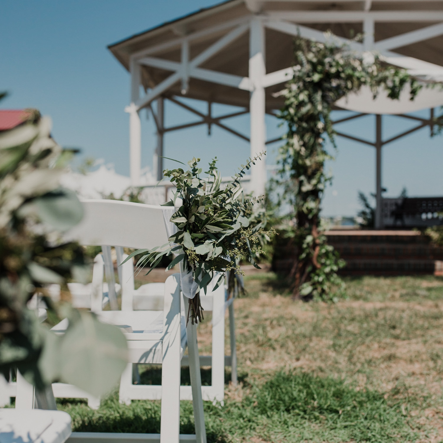 closeup of greenery decorations on wedding ceremony chairs