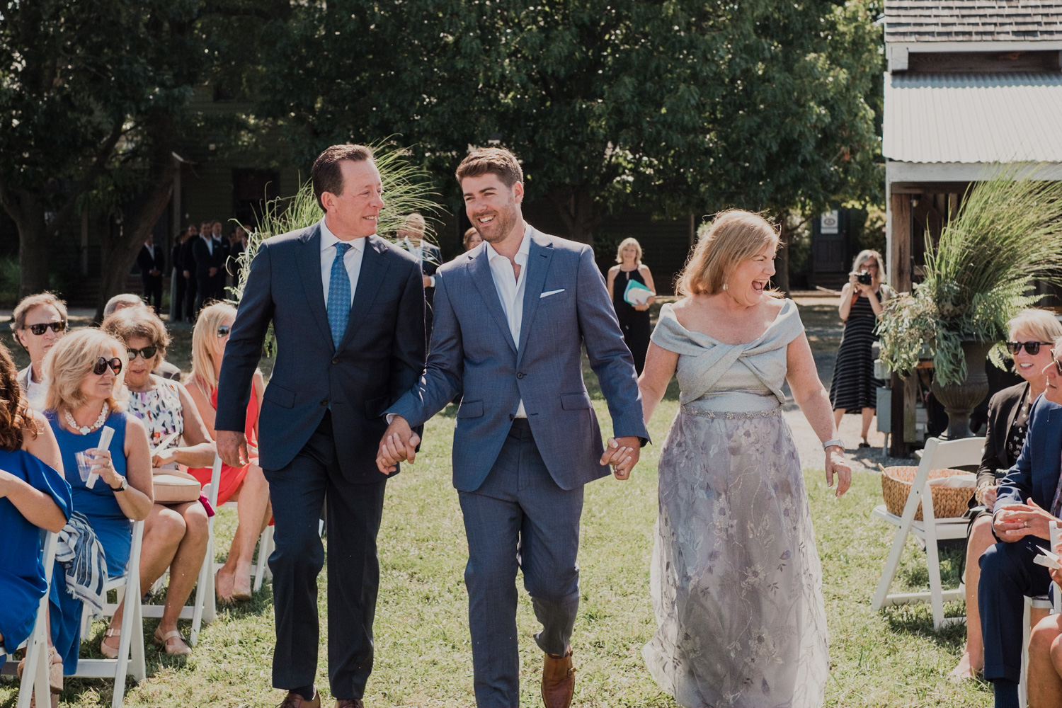 groom is escorted by both of his parents down the aisle at the start of wedding
