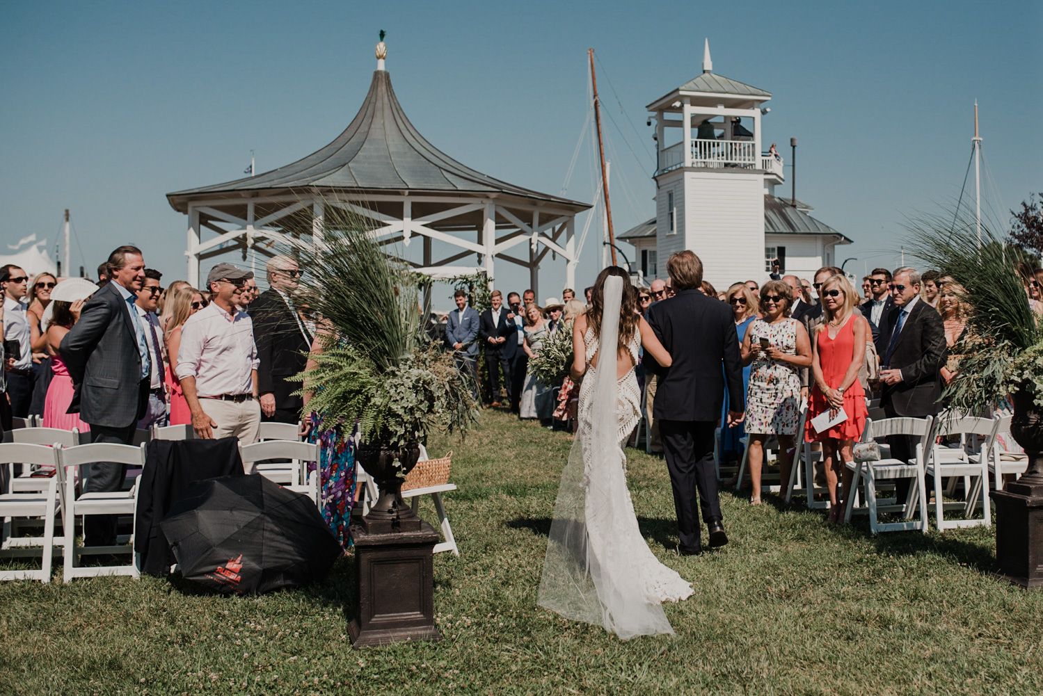 bride and her father walk down the aisle with all of the guests and the groom in the background