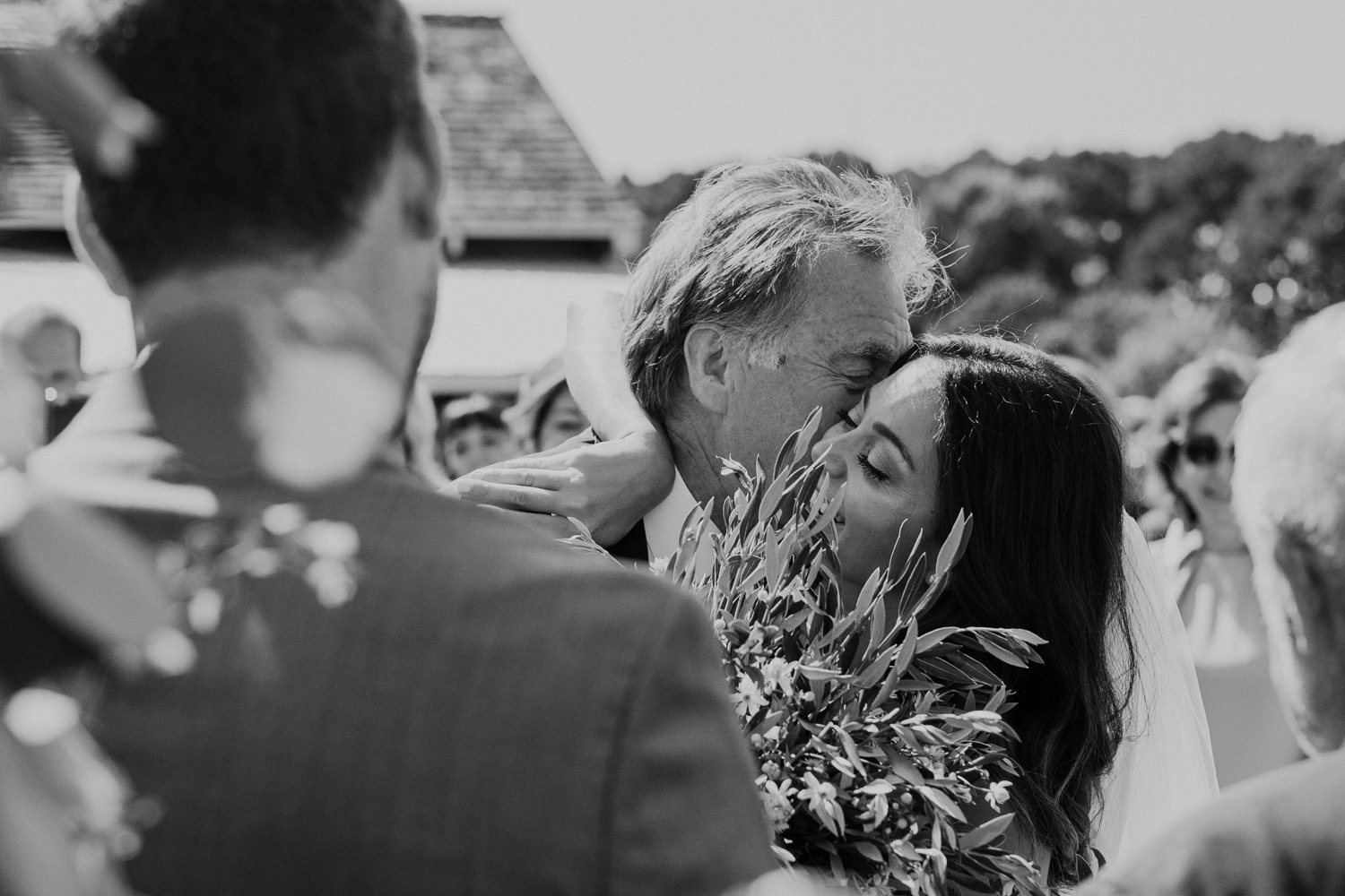 bride embraces father as he gives her away at the end of the aisle during wedding
