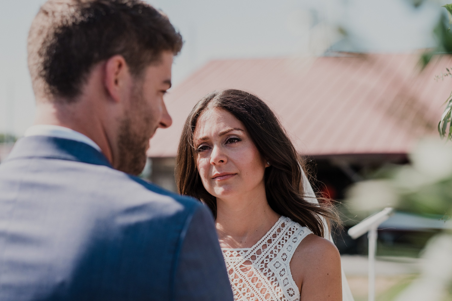 bride looks lovingly at groom during wedding ceremony