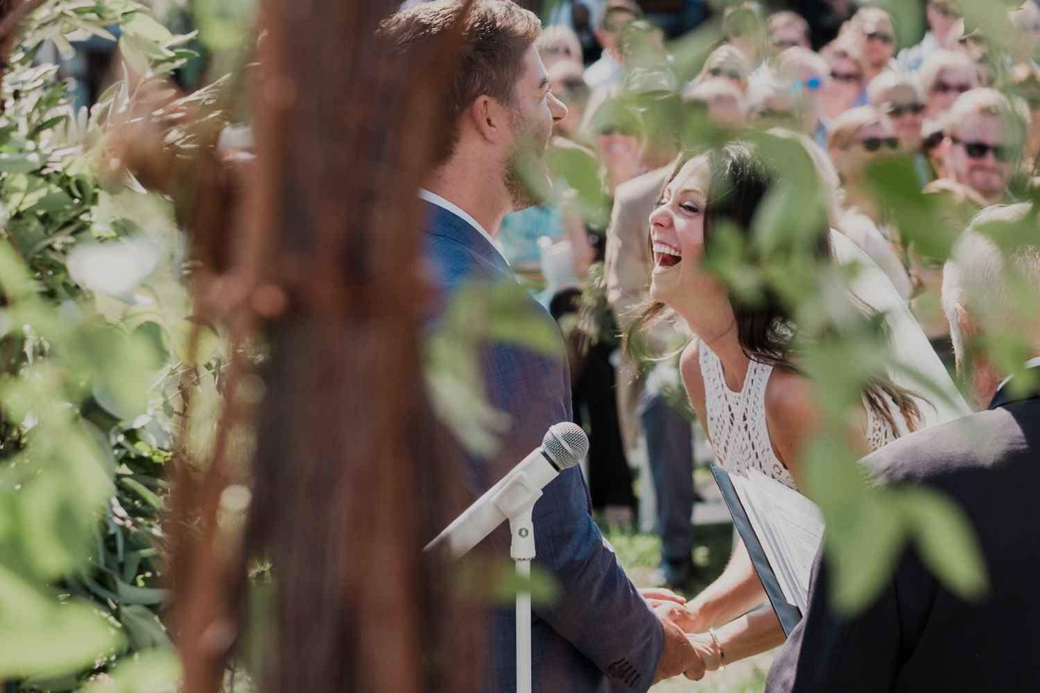 bride and groom laugh big during wedding ceremony as they exchange vows