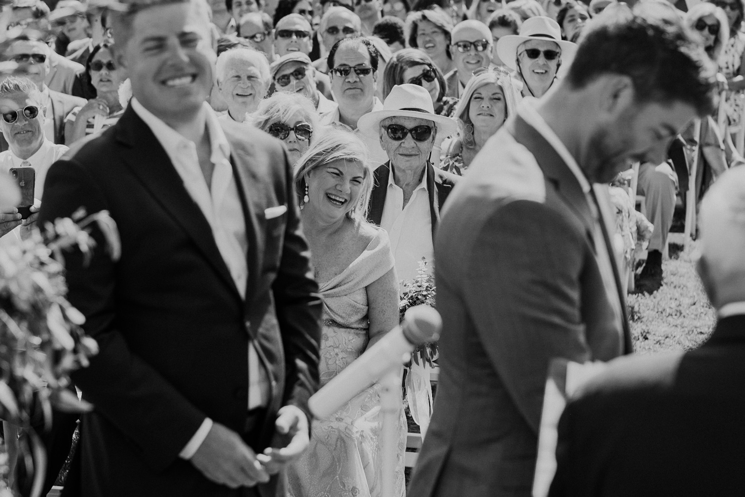 Groom's mother smiles as she watches her son get married during the vows