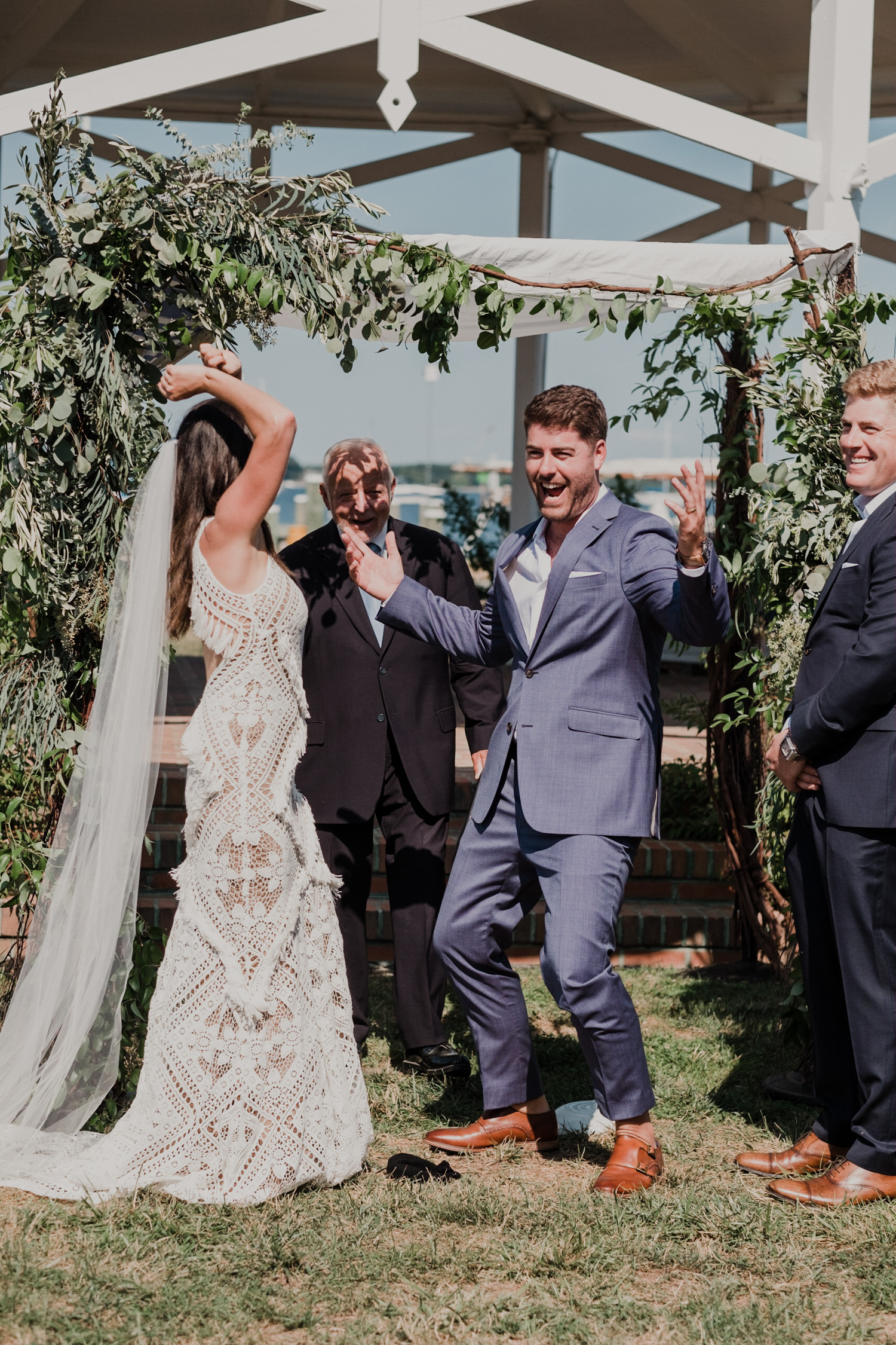 bride and groom lift their arms in celebration after the breaking of the glass at the end of the wedding