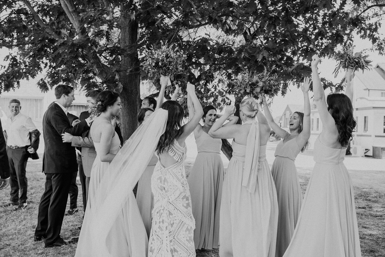bridesmaids lift their hands in celebration at the end of the wedding ceremony