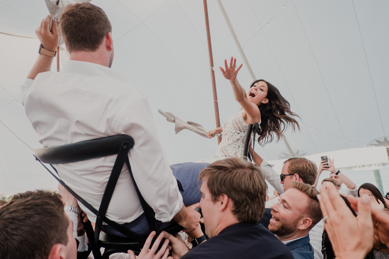 bride and groom reach for each other while lifted on chairs during the hora dance
