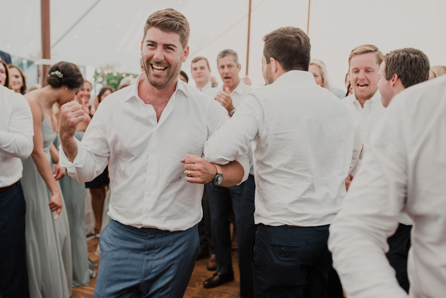 groom dances with guests during the hora