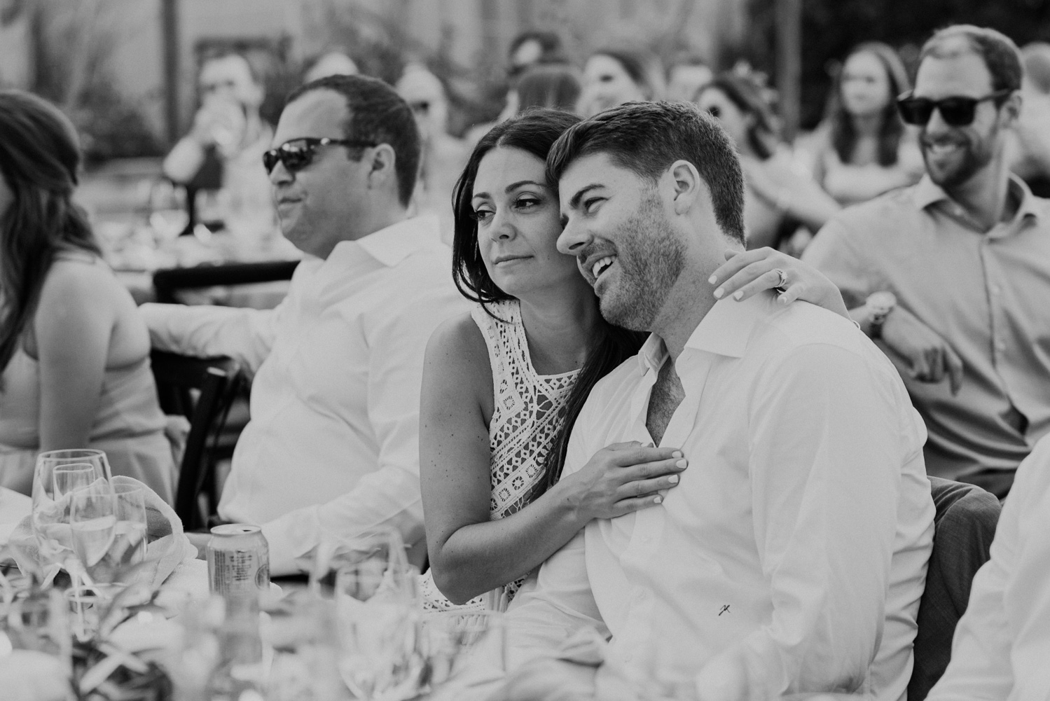 bride and groom hold each other close while listening to toasts