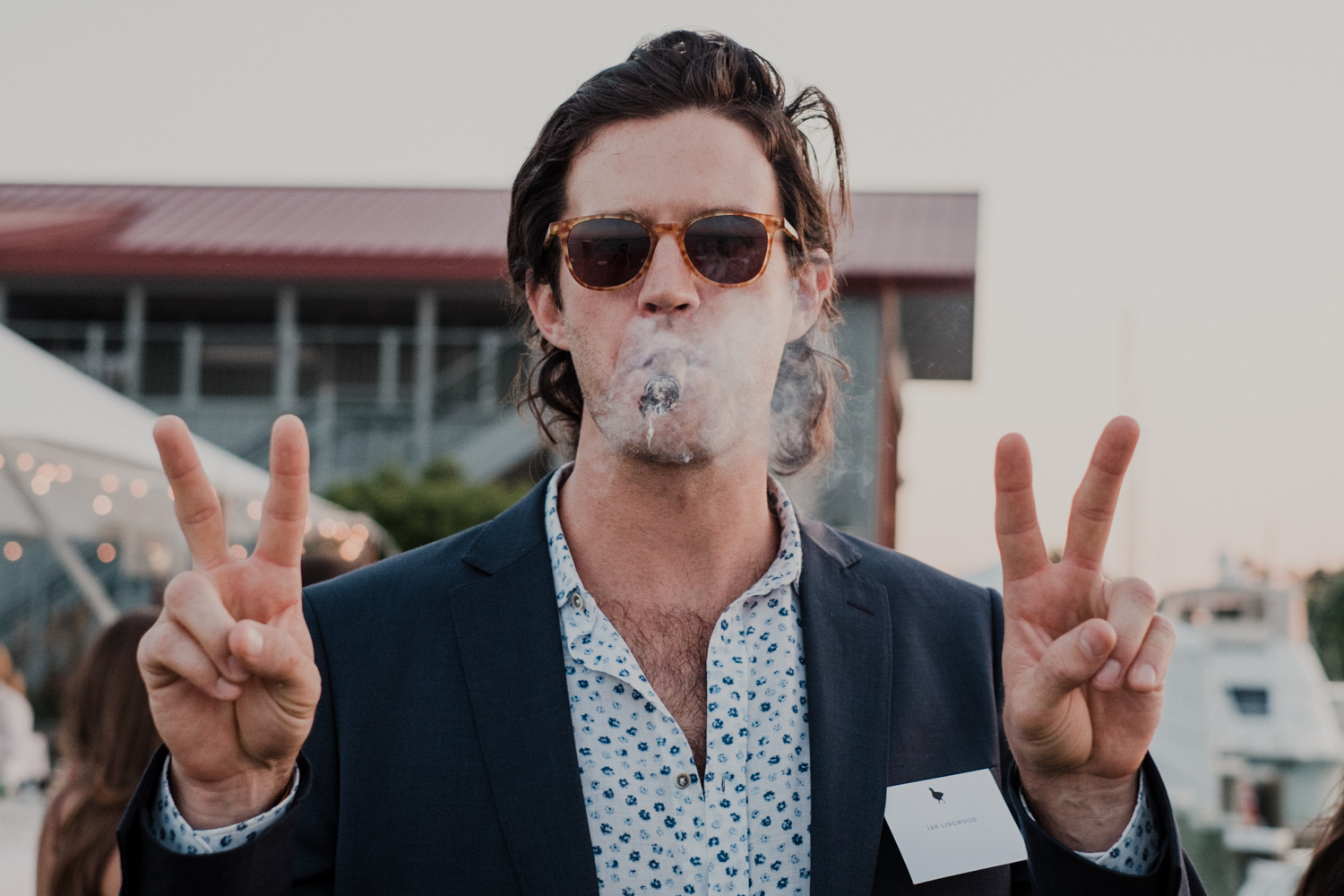 wedding guest smokes cigar and holds up double peace signs