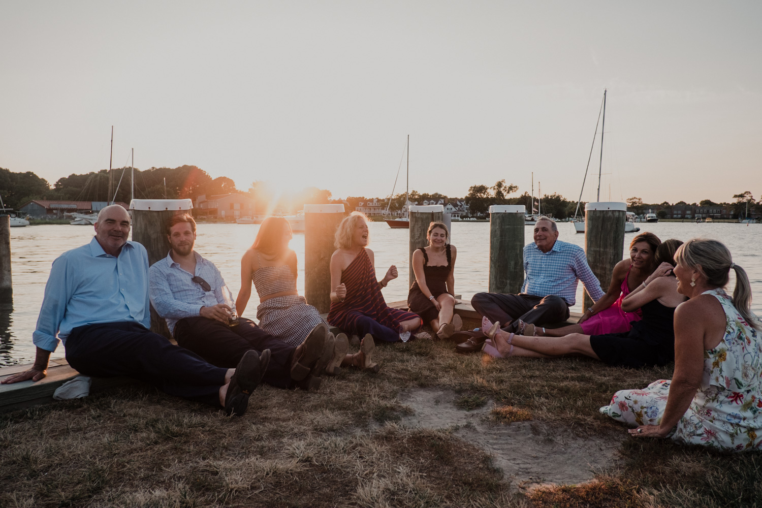 wedding guests sit on the docks during sunset relaxing at the Chesapeake Bay Maritime Museum