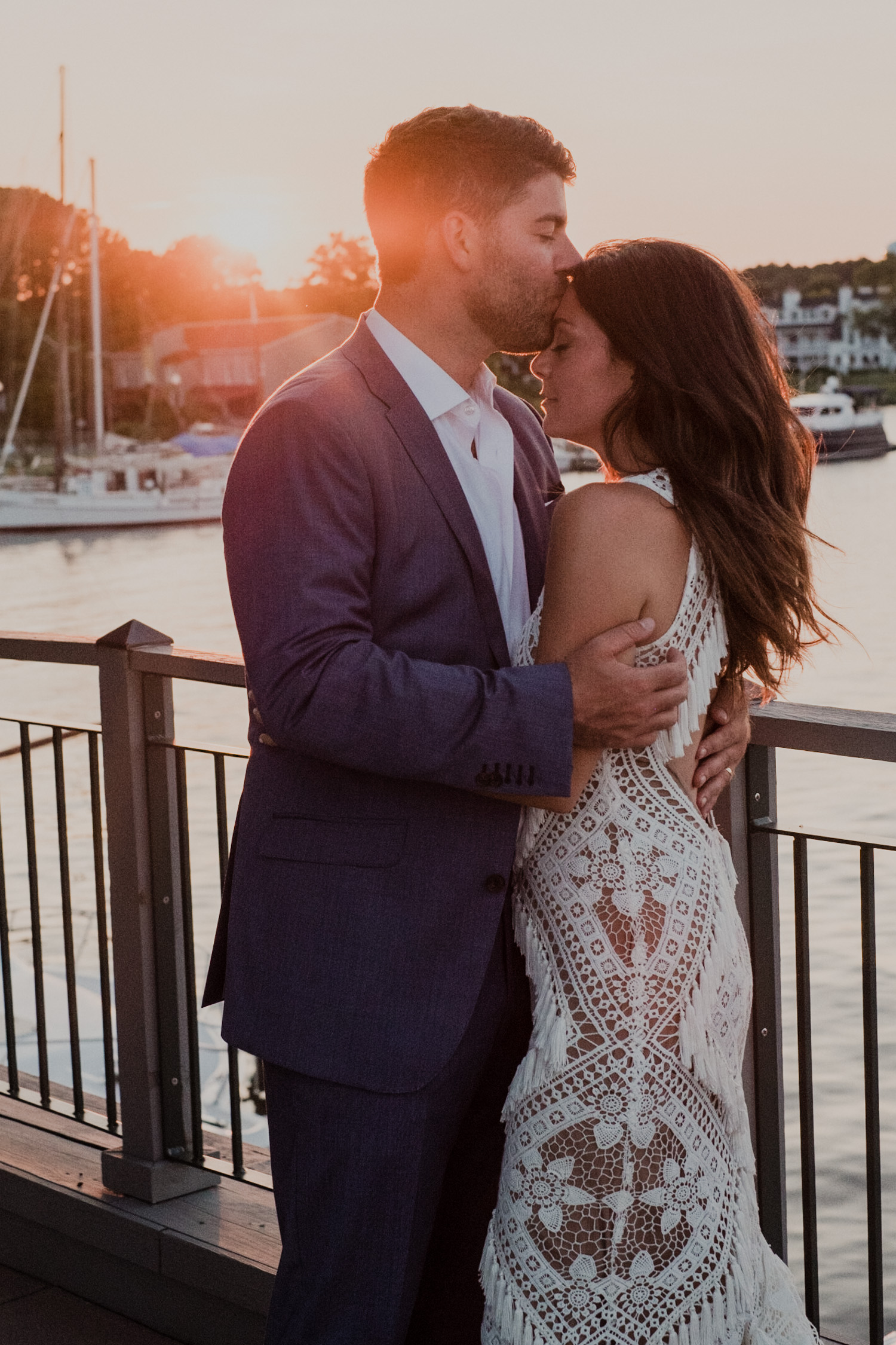 groom kisses bride's forehead during sunset portraits