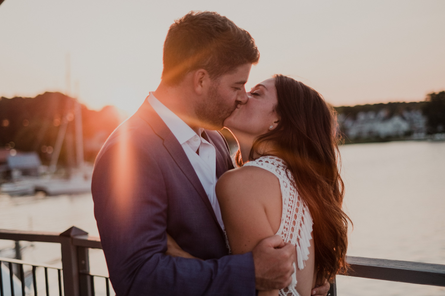 bride and groom kiss during sunset portraits with the bay in the background