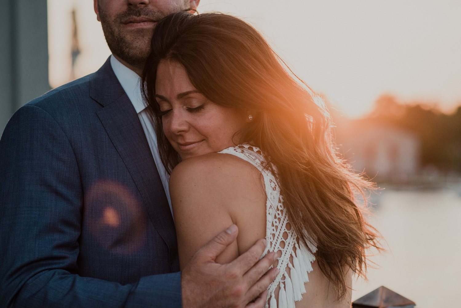 up close as bride and groom embrace at sunset