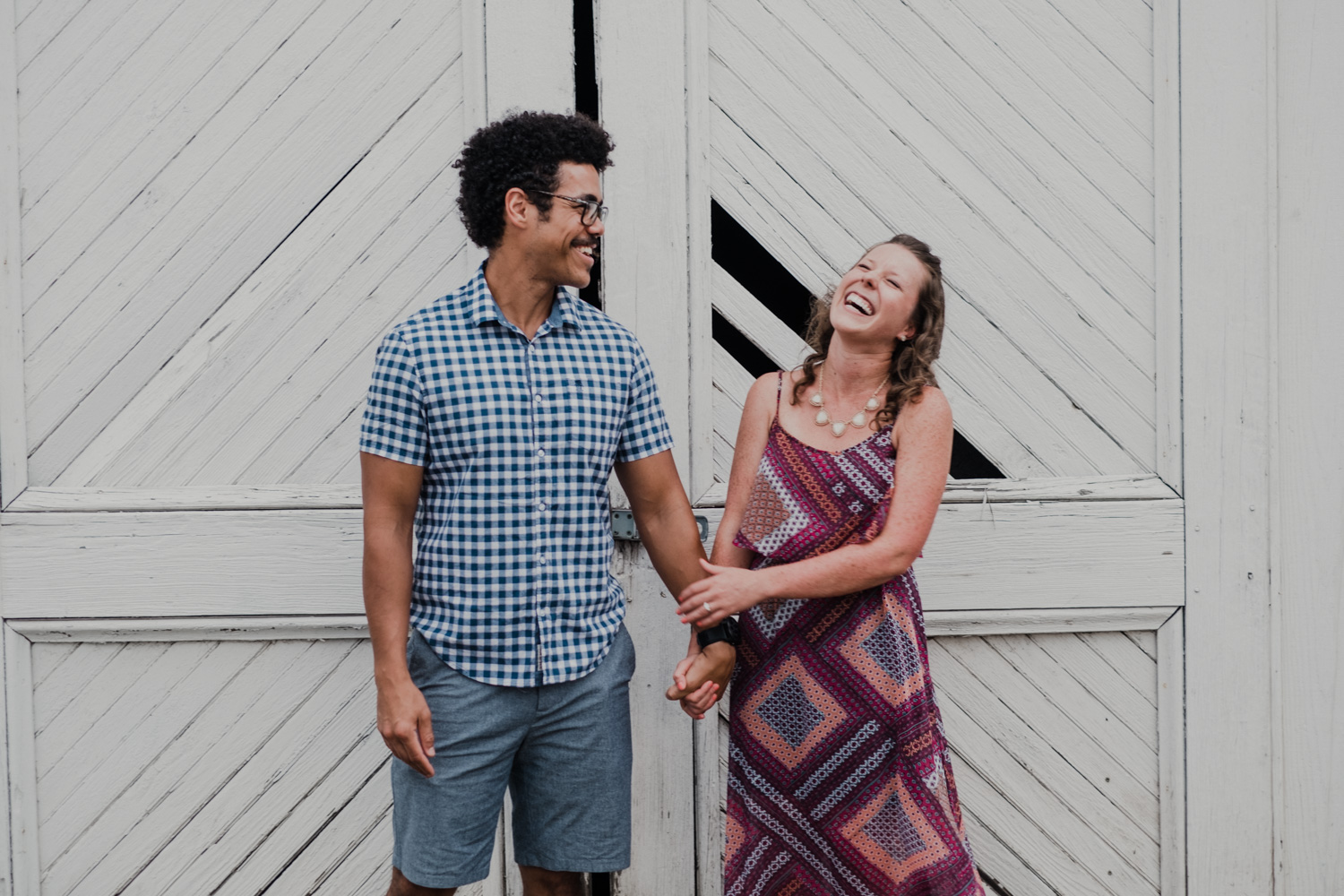 engaged couple laughing while holding hands in front of old white doors