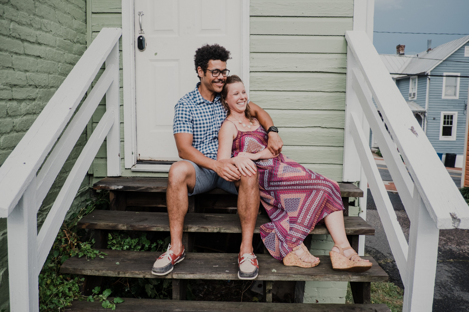 engaged couple holds each other on a wooden stairway