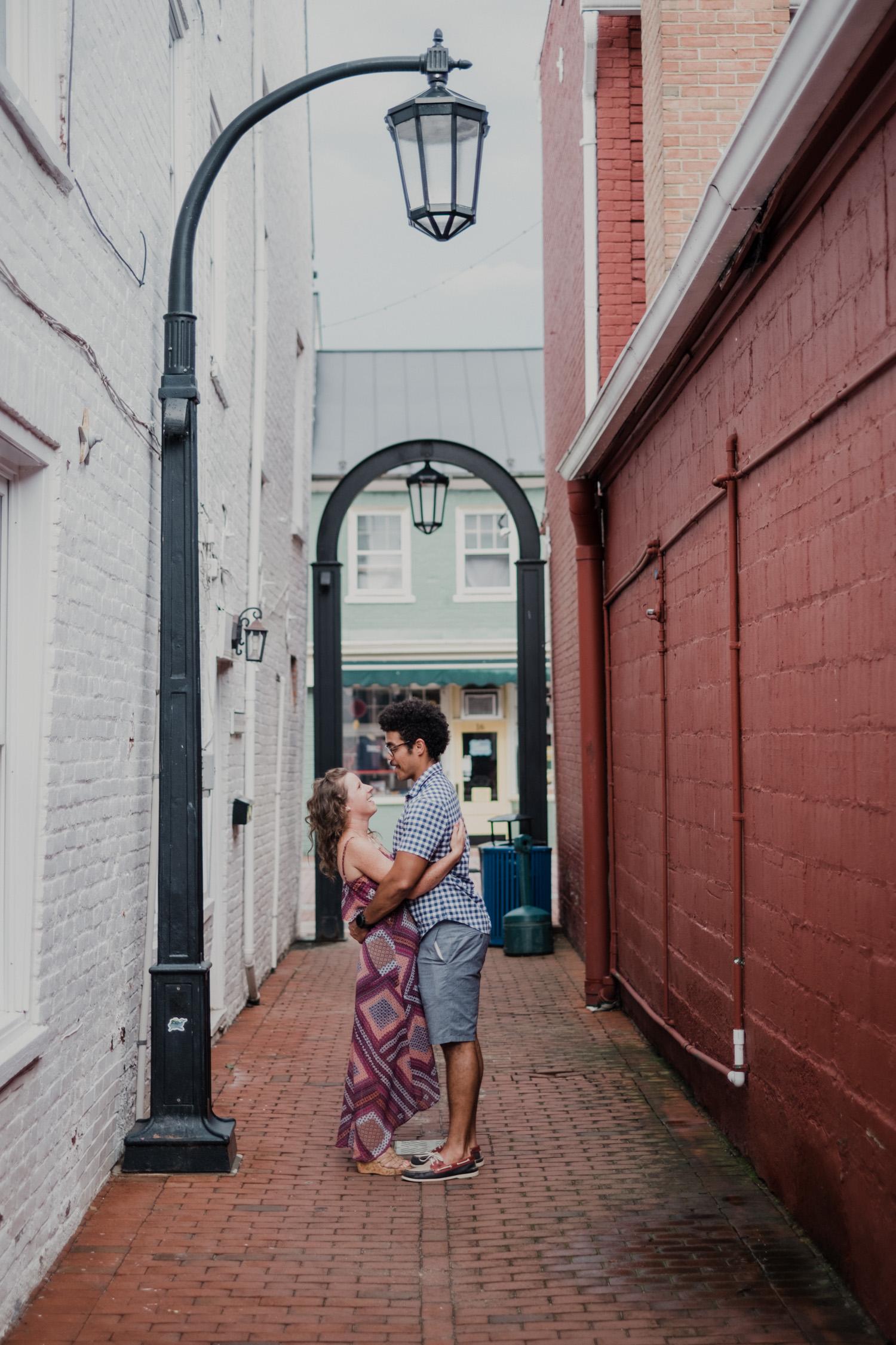 engaged couple embracing in Leesburg alleyway underneath lamp post