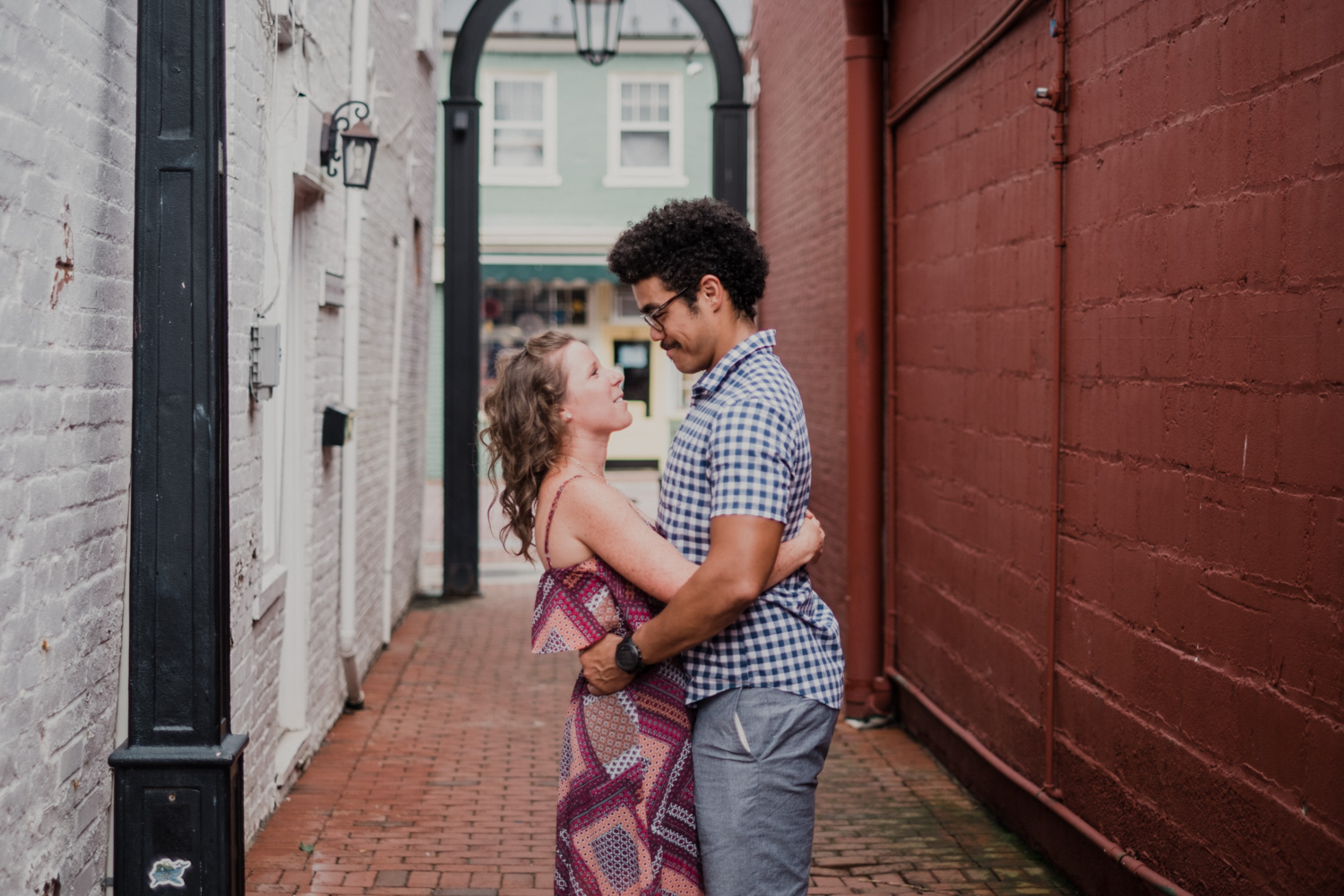 couple holds each other during engagement photos in a Leesburg alleyway