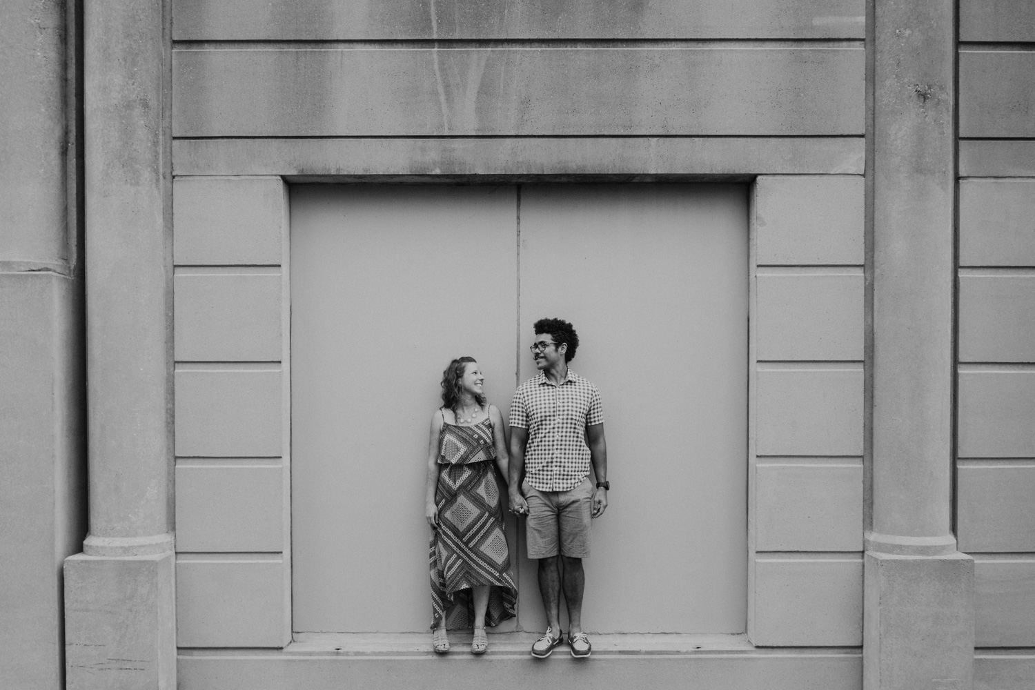 couple stands on a ledge on a concrete wall while looking at one another