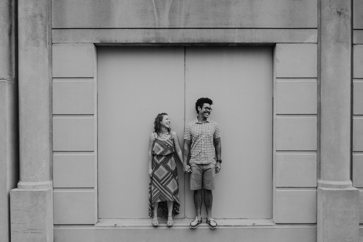 Couple stands in framed concrete wall laughing
