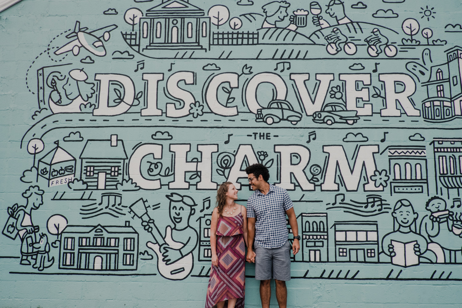 Couple stands side by side in front of Discover The Charm Leesburg mural while smiling at each other
