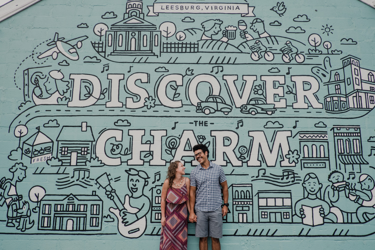Couple laughs standing in front of Leesburg town mural