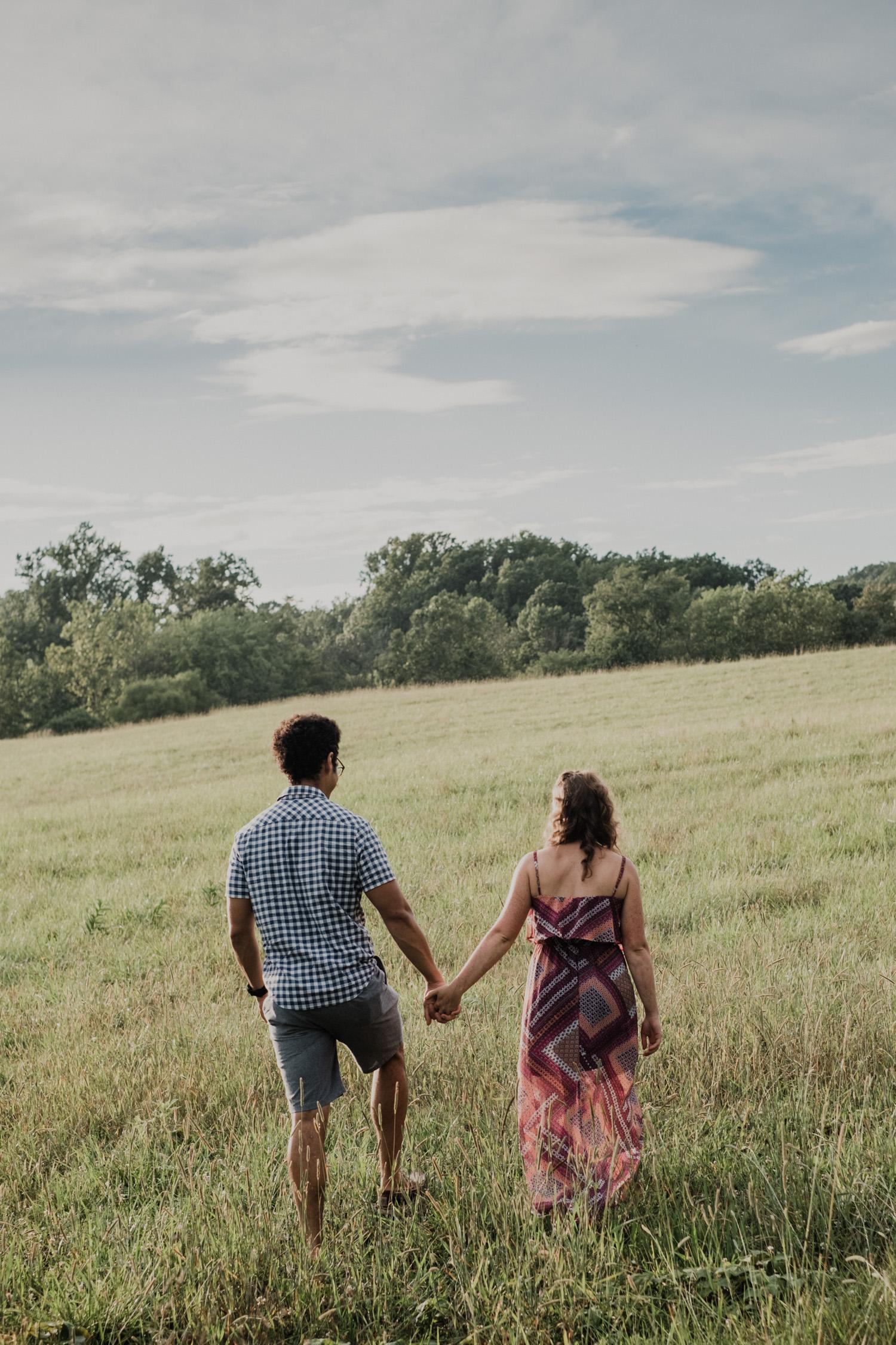 Couple walks away through a field at a park
