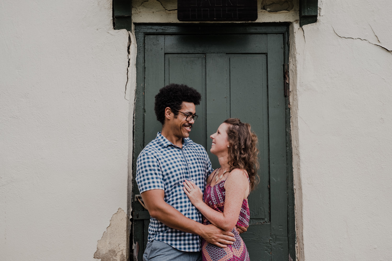 couple holds each other in front of a green door