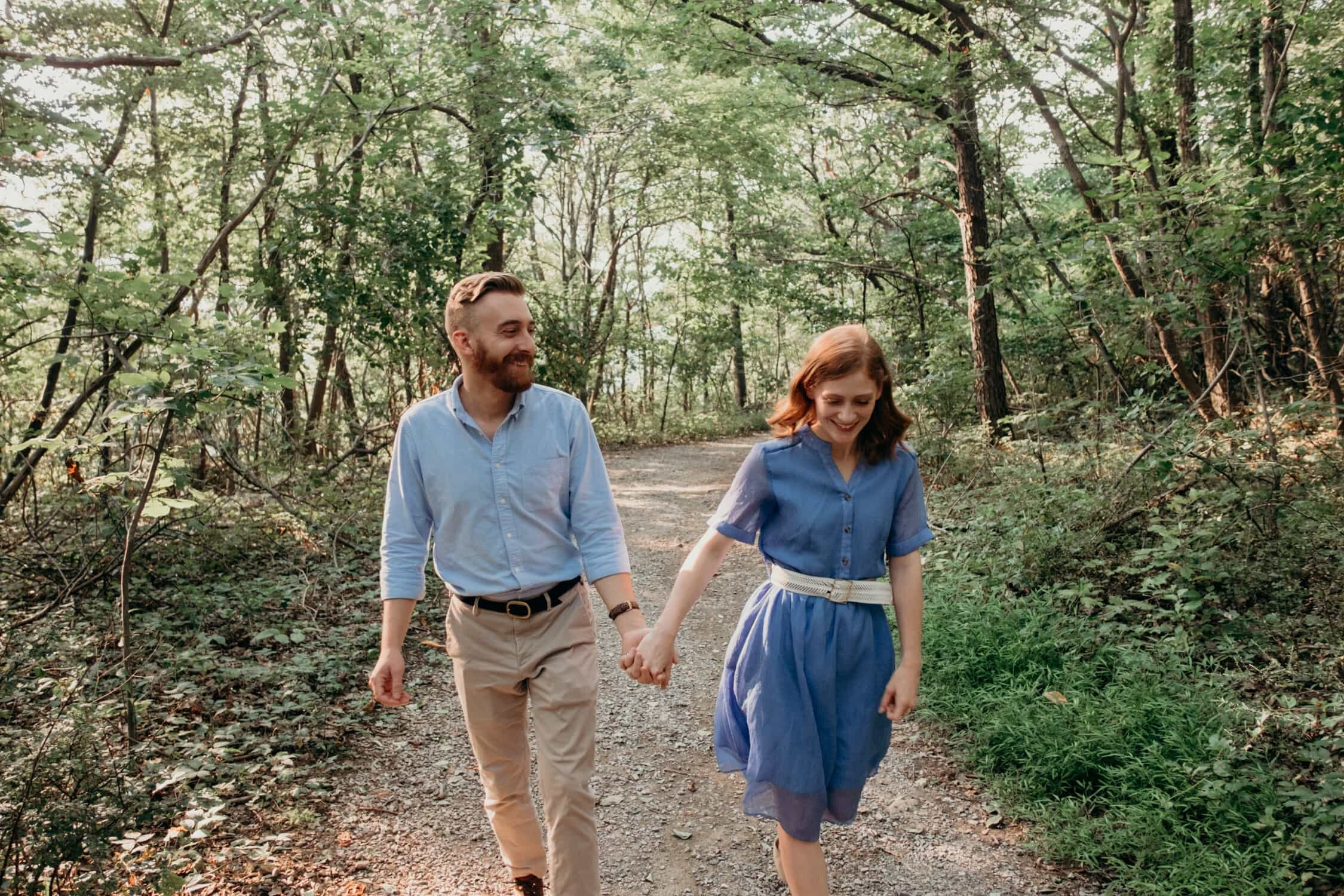 Sara and Marshall walking through the woods and holding hands at Bears Den Overlook