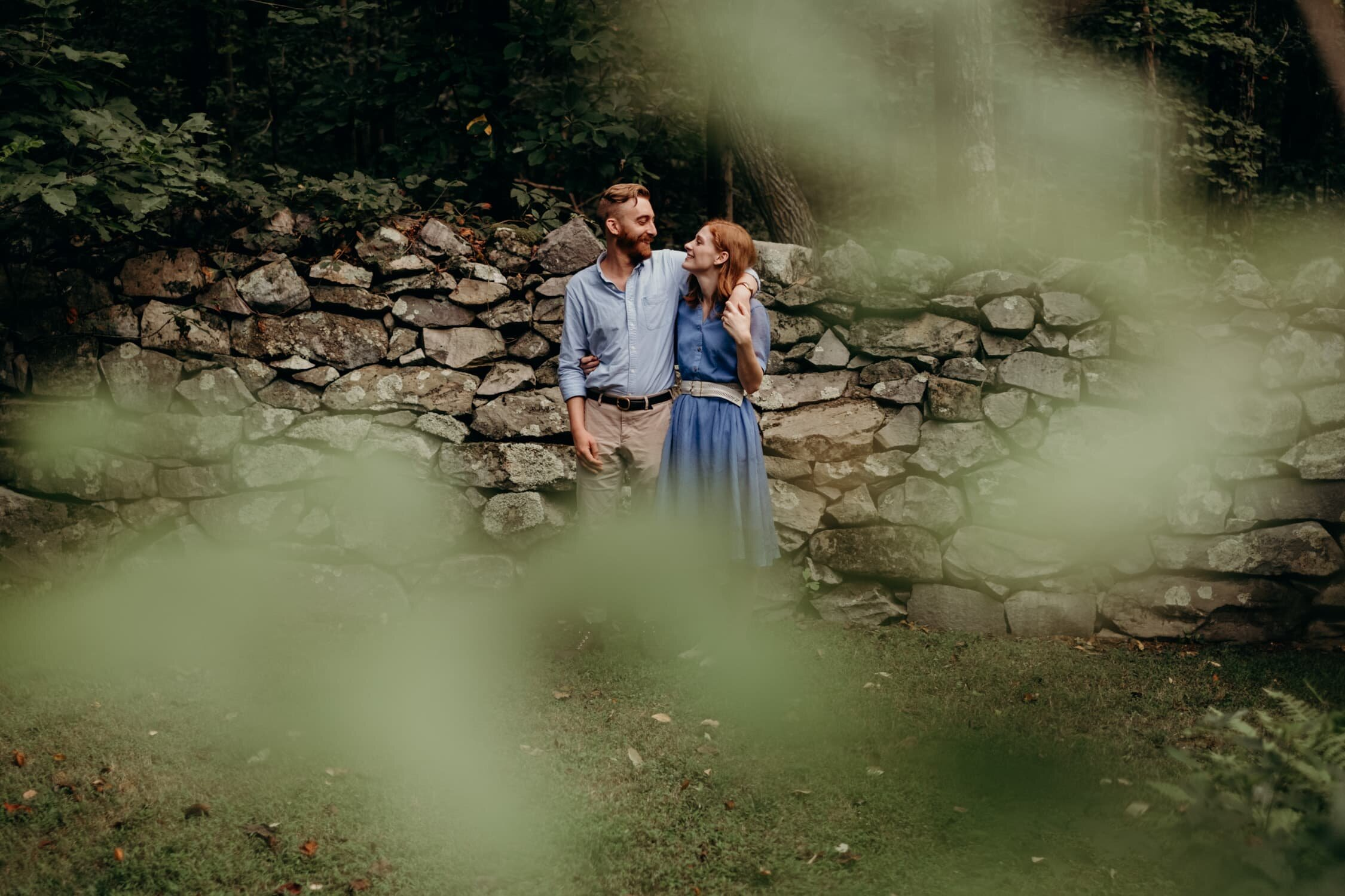 Engaged couple standing in front of a rock wall