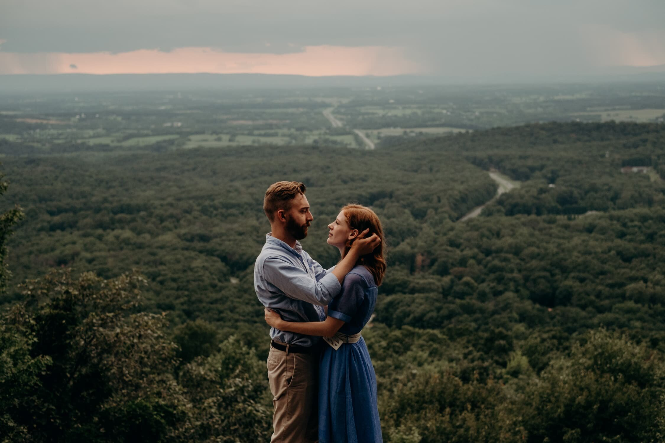 Couple holds each other on cliff with thunderstorms at sunset in background