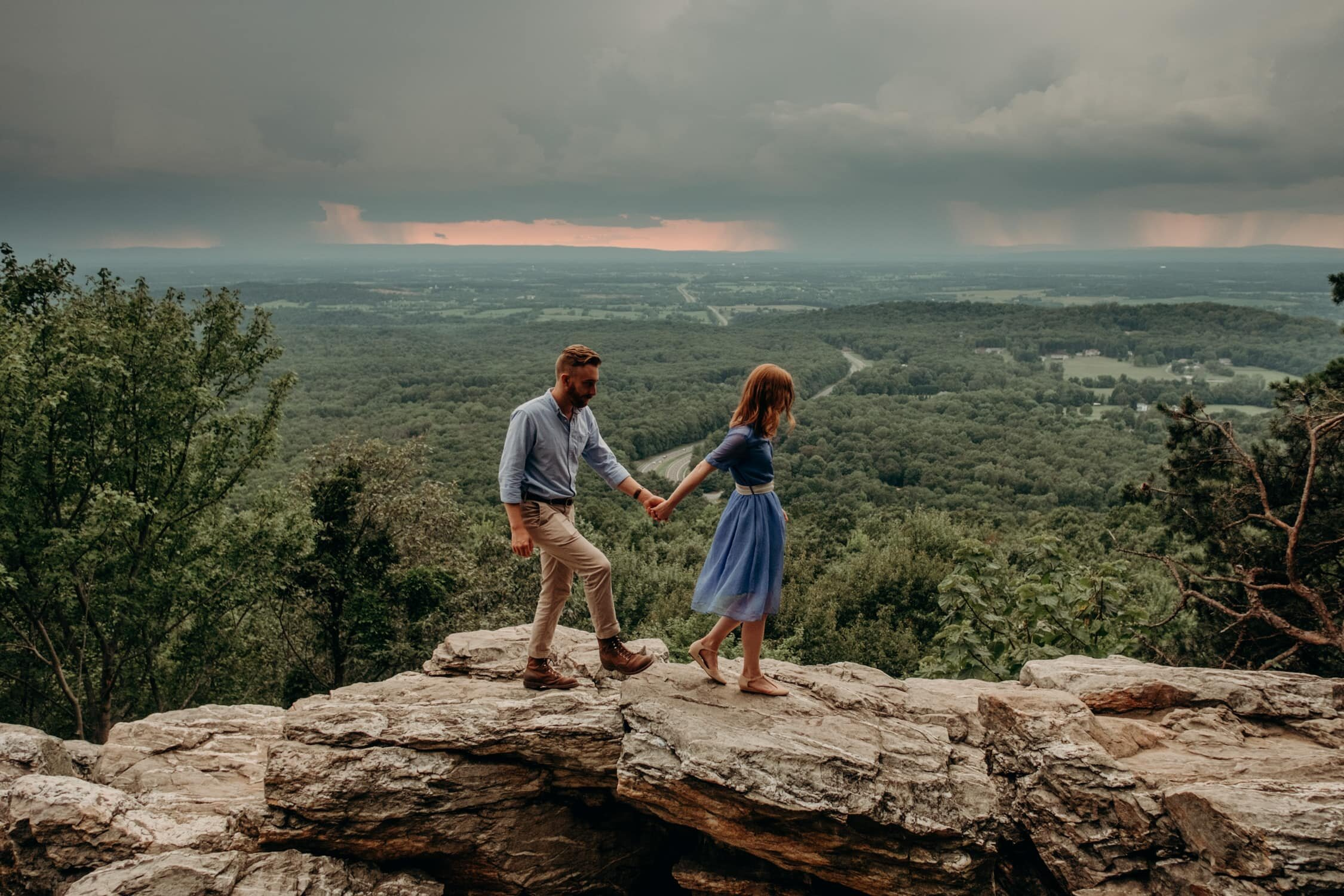 Couple walks along cliff overlooks holding hands at Bears Den Overlook