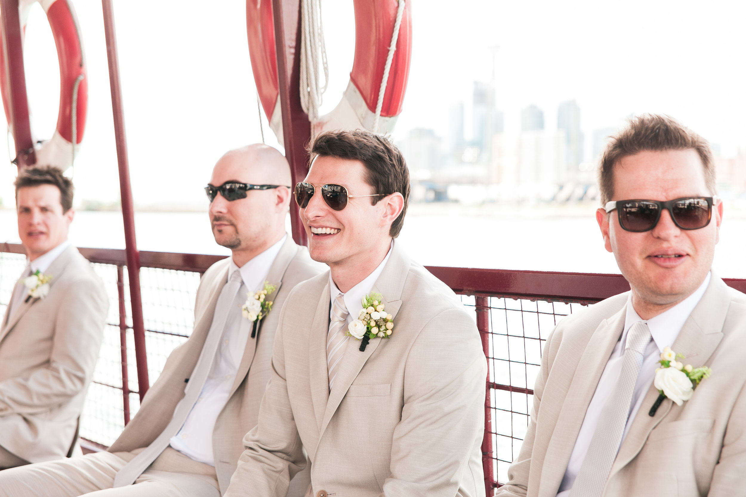 Groom and groomsmen in tan suits on boat