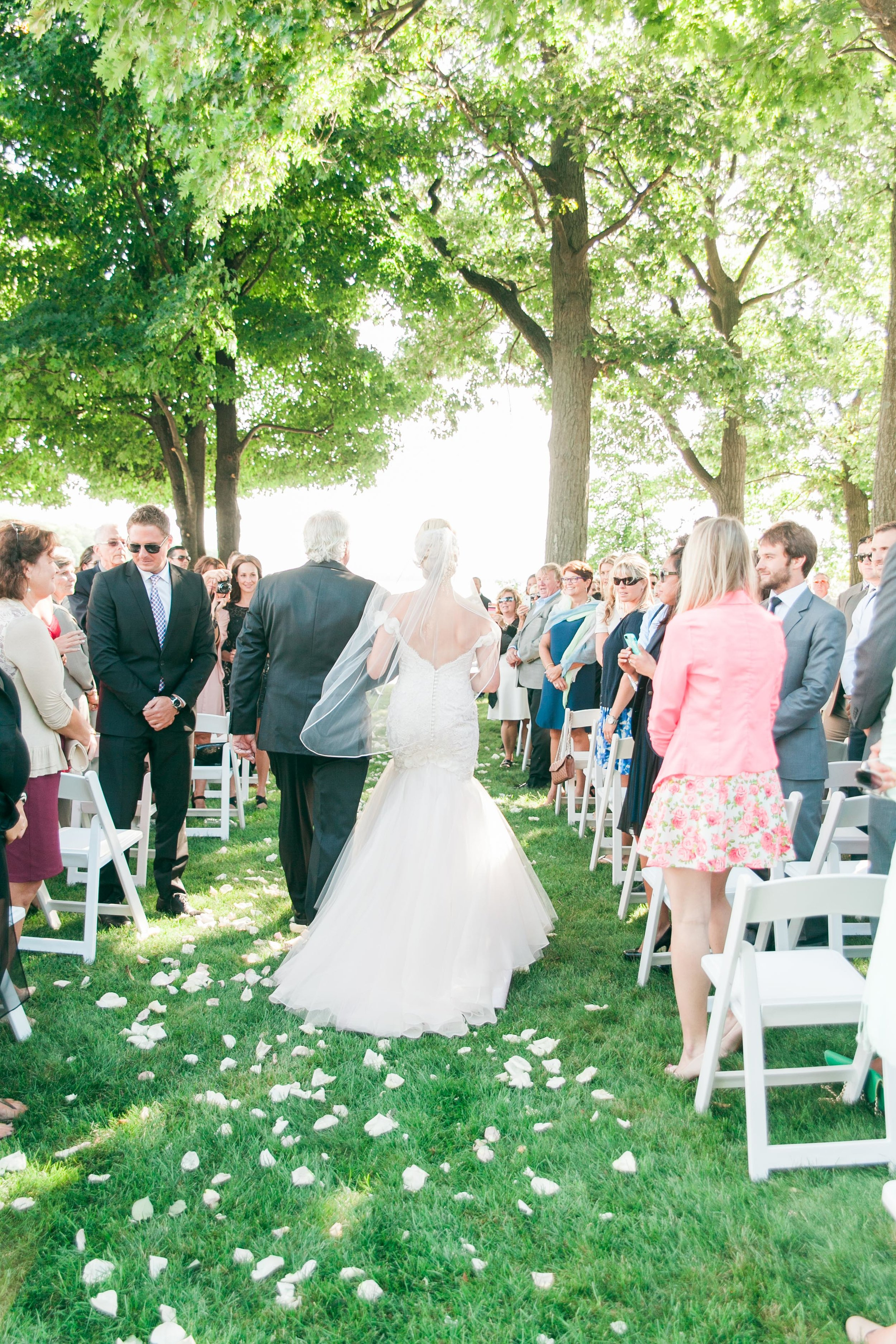 Bride walking down aisle at outdoor ceremony