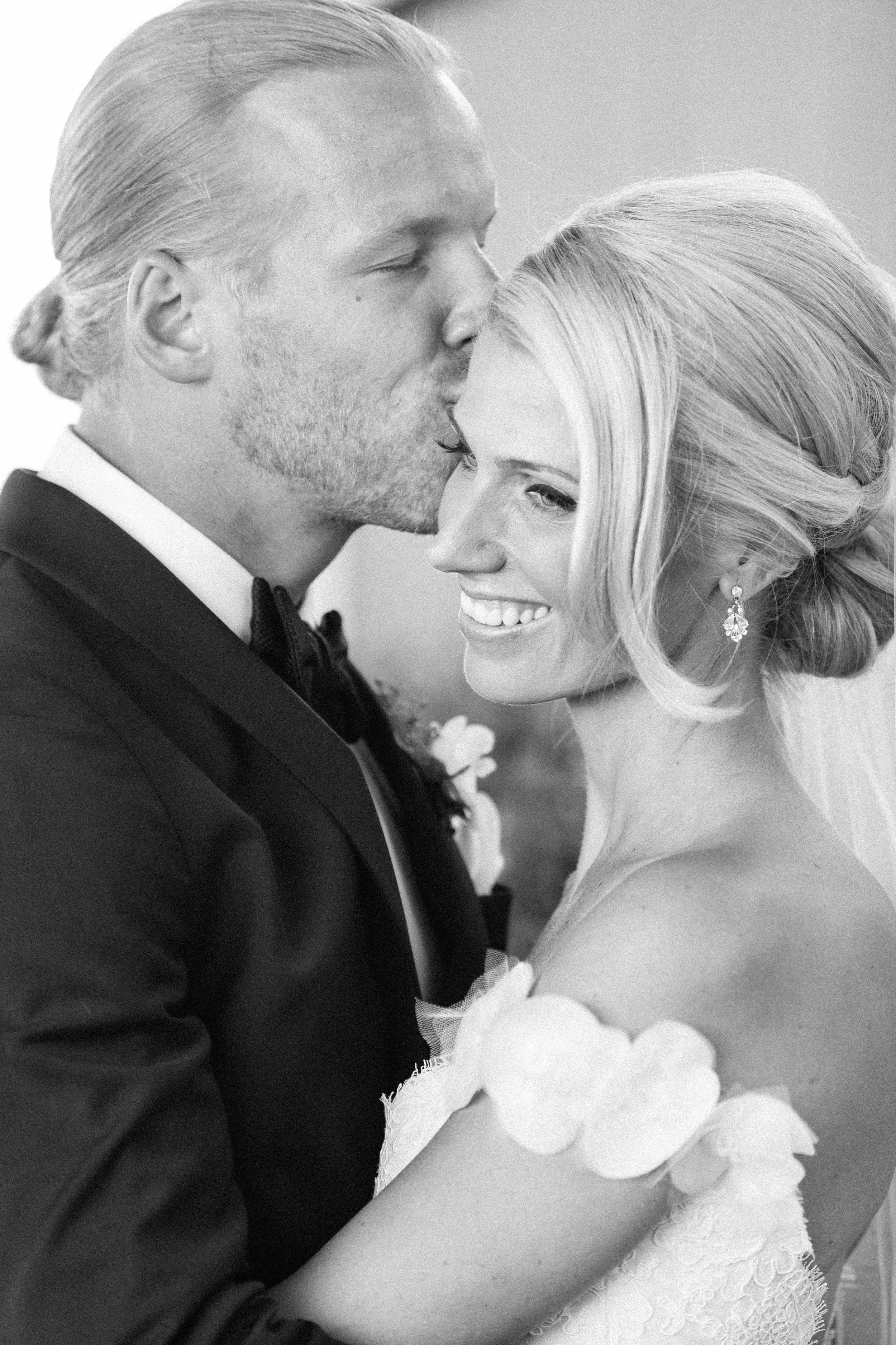 Groom kissing bride outside