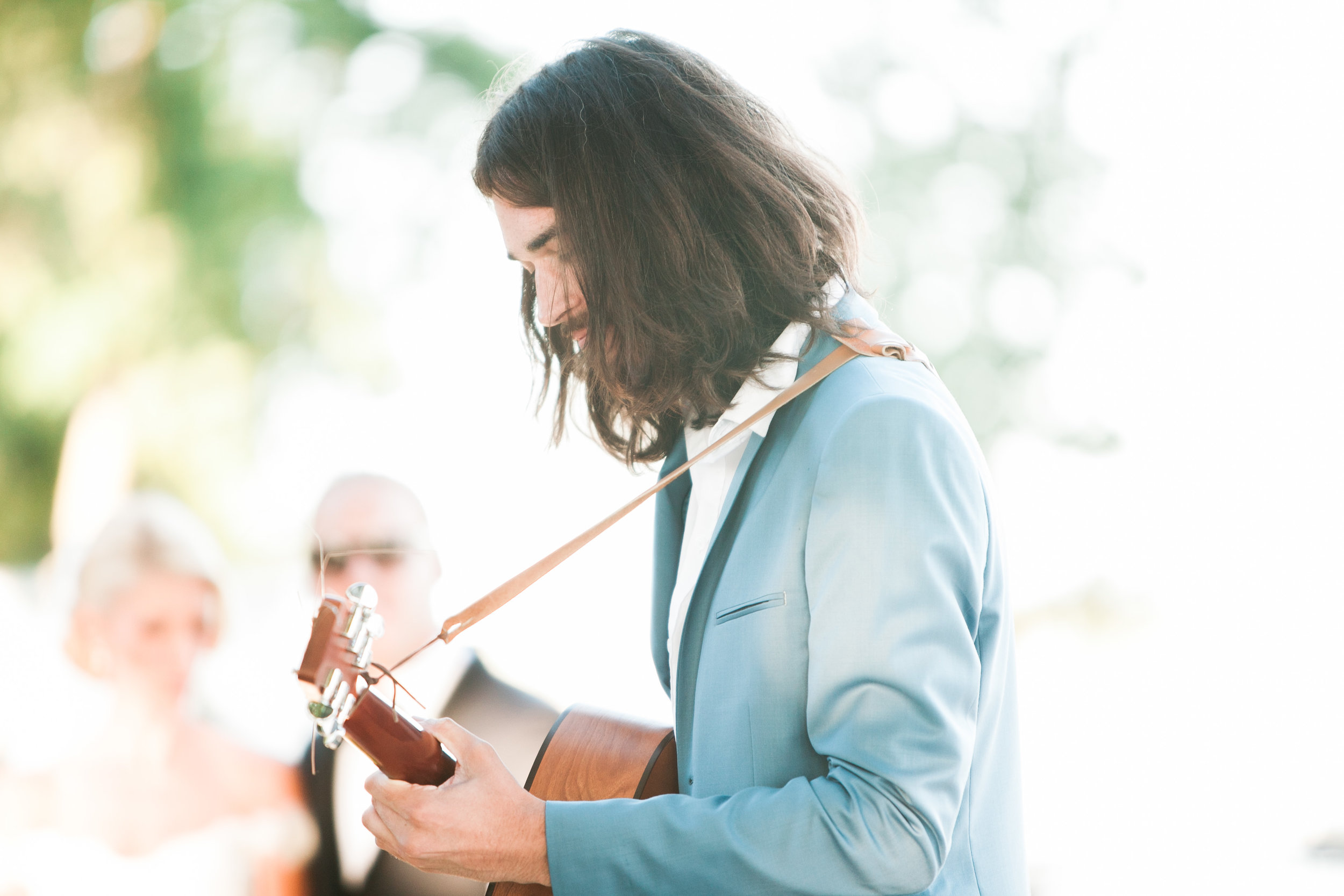 Man playing guitar at outdoor wedding