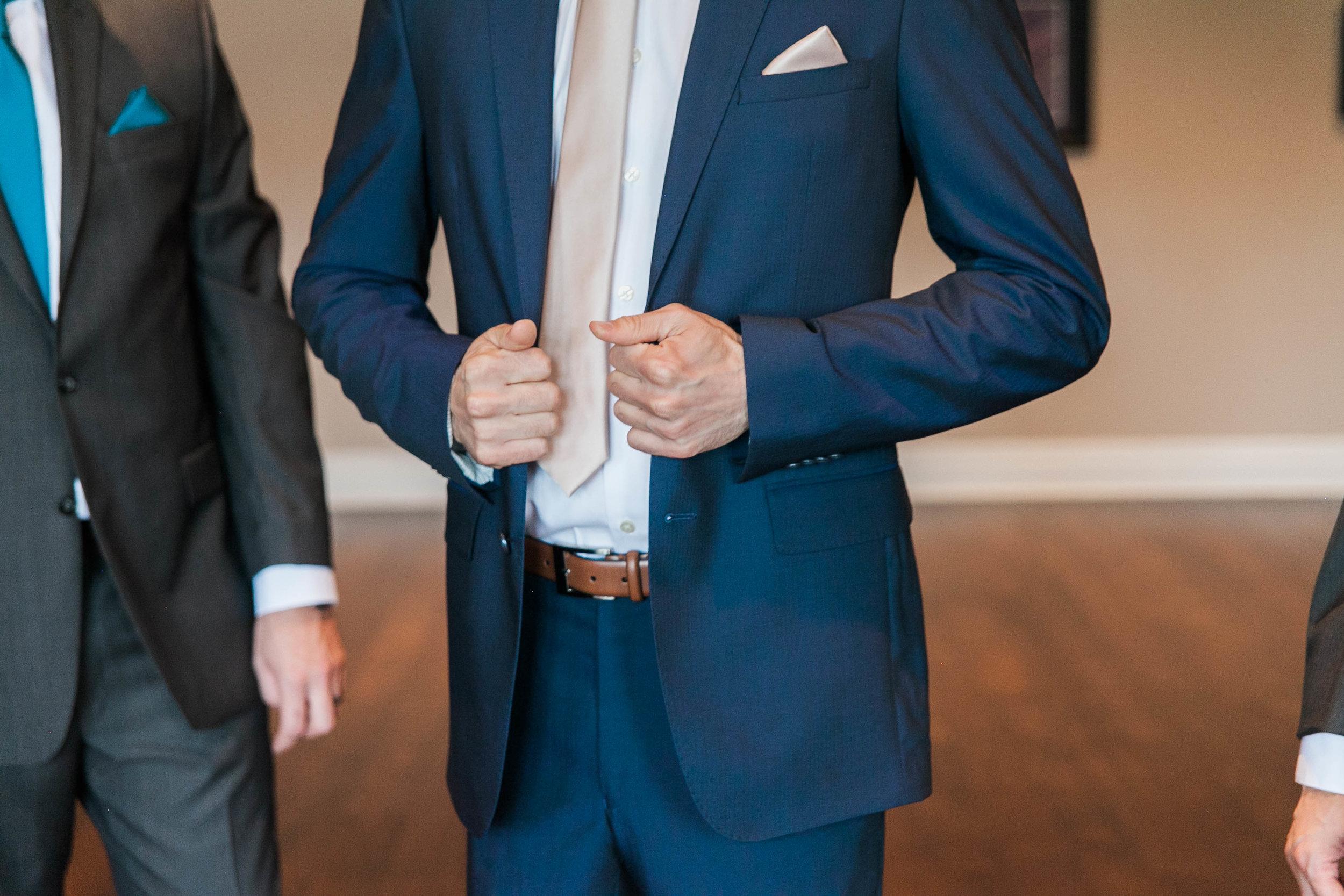 Groom adjusting suit before first look