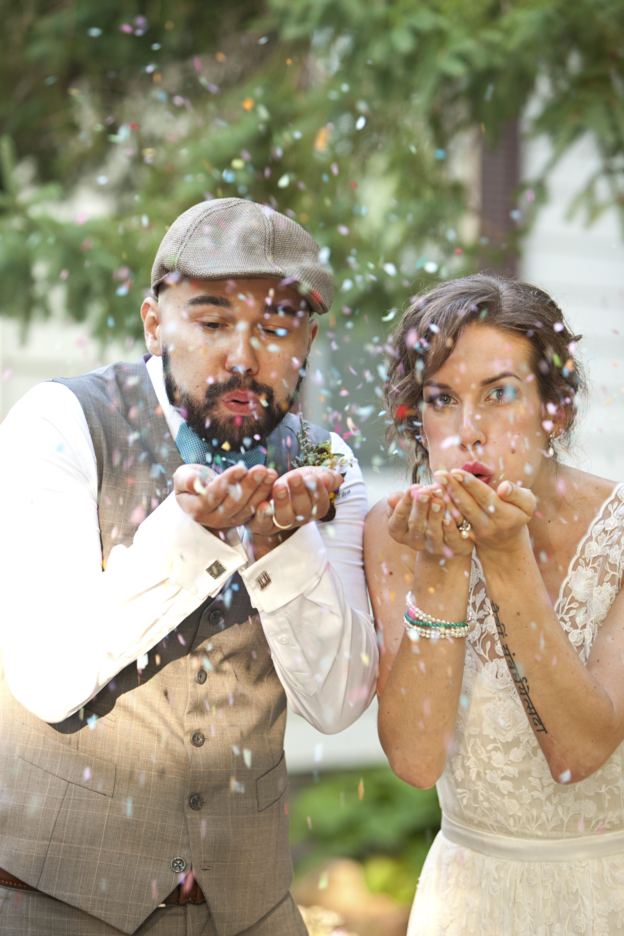 Bride and groom blowing confetti