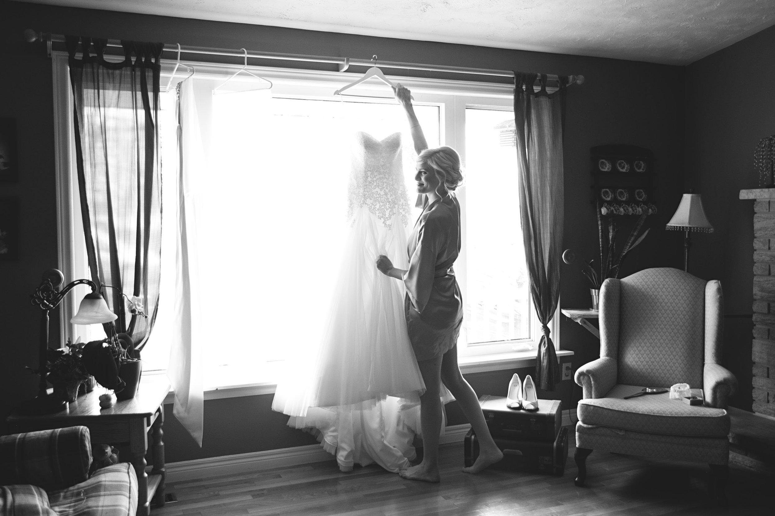 Bride putting wedding dress on