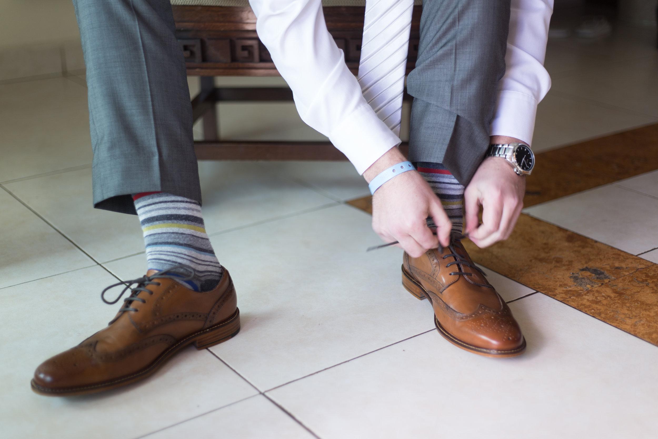 groom tying shoes on wedding day