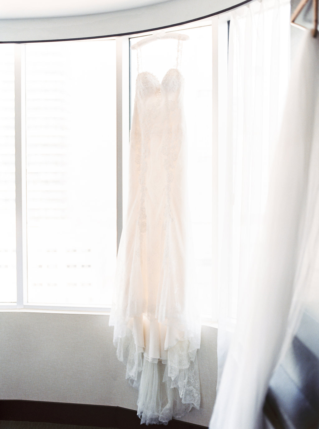Lace wedding dress hanging in window.