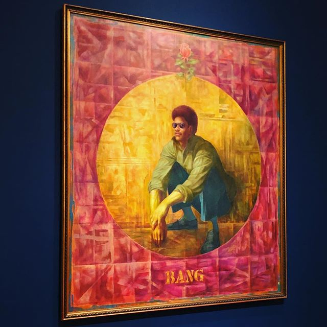 """BANG Charles White """"Banner for Willy J"""" (1976) [a painting of a man wearing sunglasses, khaki shirt and teal pants kneels within a gold mottled circle on a red mottled background, a single red rose stem floats above his head, the word BANG is stenciled in gold in the lower thirds of the painting.] A painting that memorializes Charles White' cousin Willy J., who was killed as an innocent bystander during a bar robbery. Show closes end of the week 🌹See it if you can. #charleswhite"""