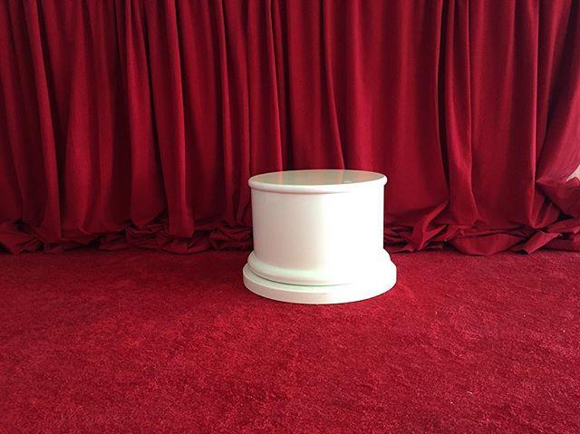 an ivory cylindrical pedestal, a deep red carpet, a deep red curtain walk into a bar #bts #puddlepower