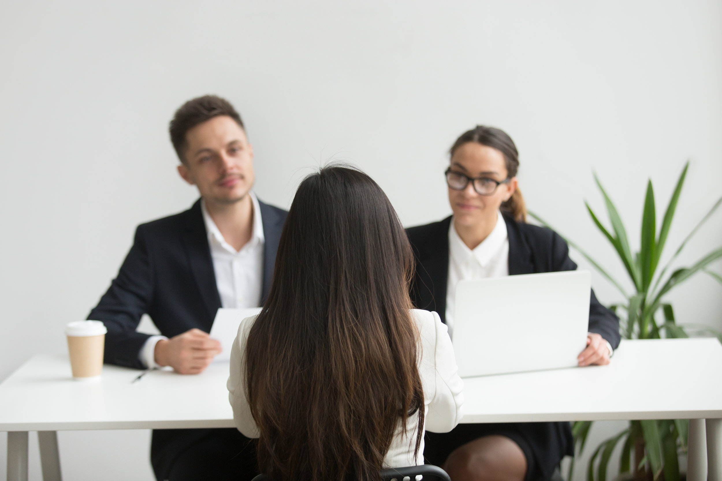 Image description: A women is seated in front of a desk being interviewed by two executives, one female and one male. Photo source:  Yanalya/Freepik