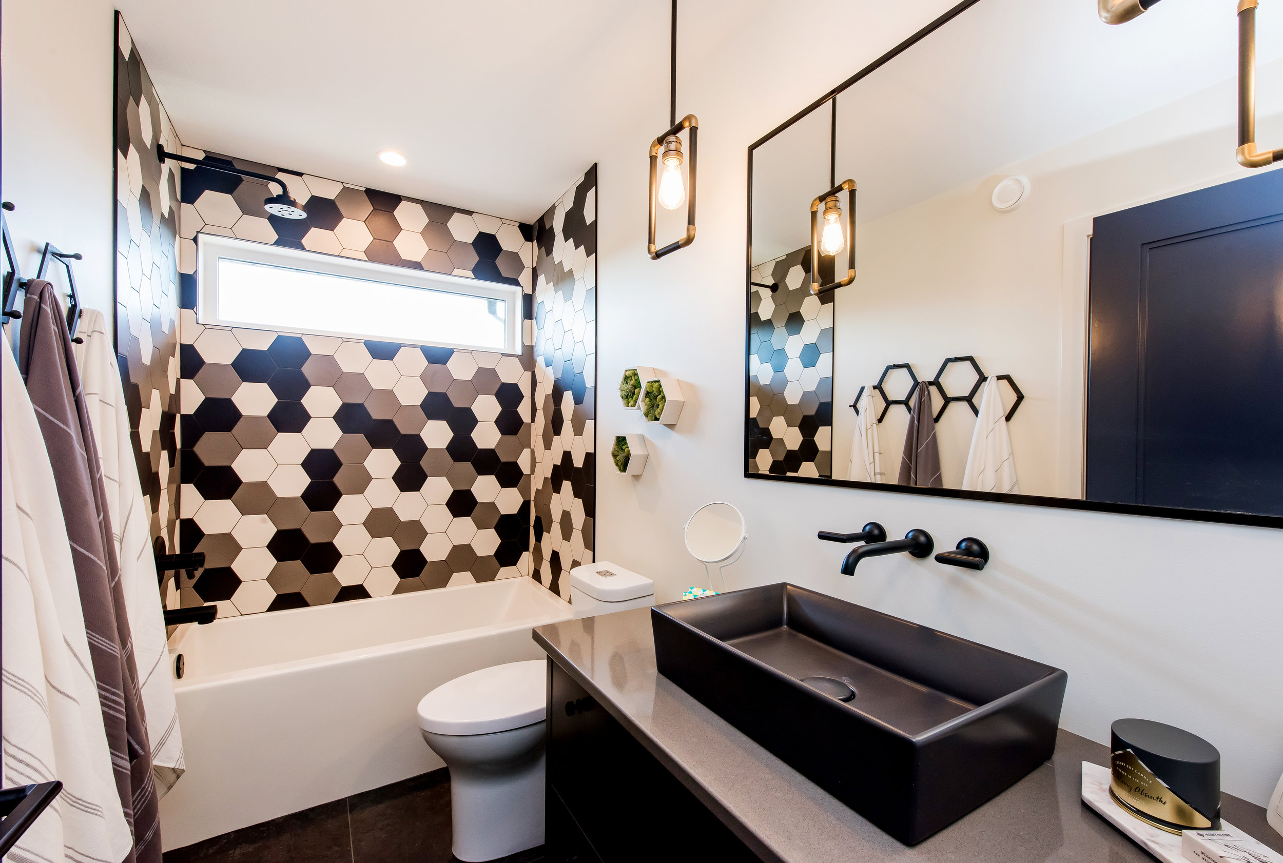 Okay, we admit – we may have an obsession – note the geometric towel rack, and hexagon moss wall hangings that tie in perfectly to the multi-coloured hexagon shower tile...can't have too much of a good thing right?