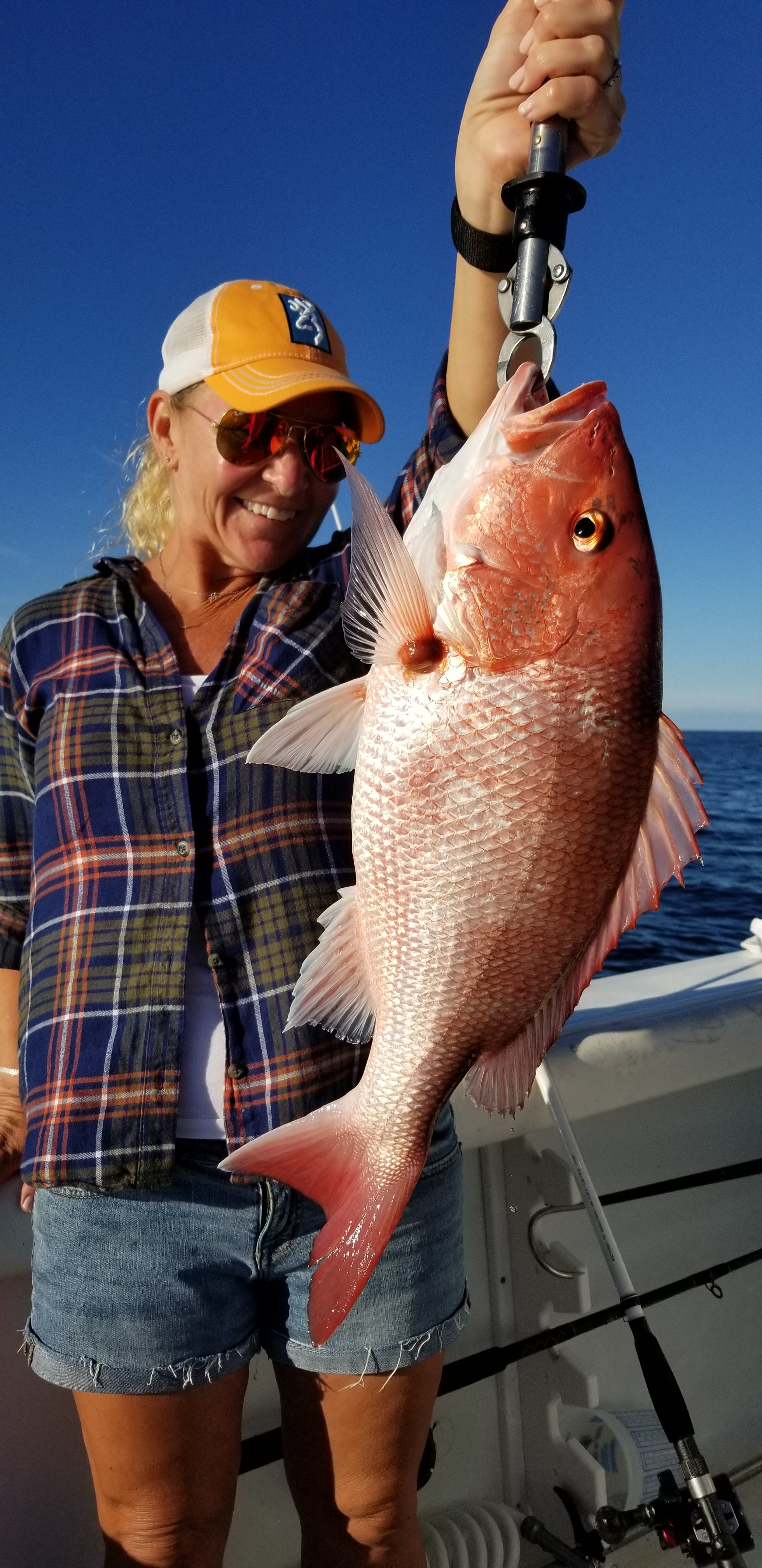 woman holding red snapper catch