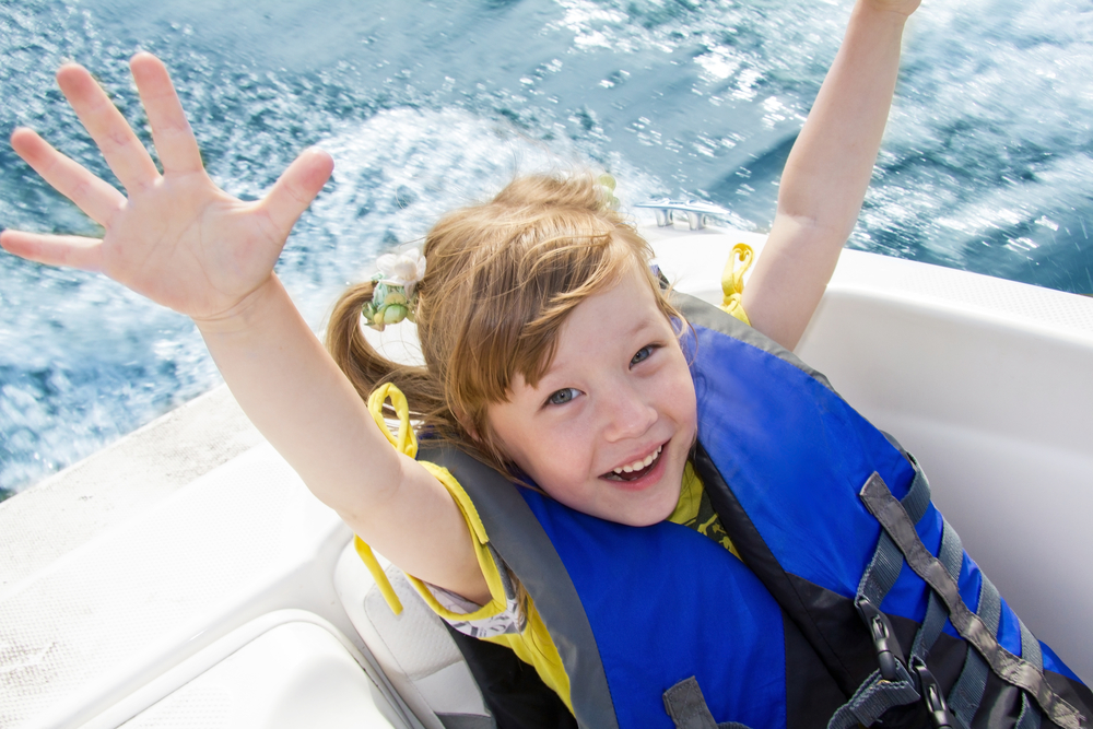 child on boat having fun with hands in the air